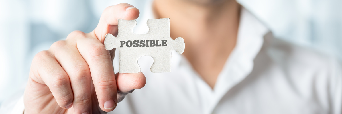 Businessman holding puzzle piece with Possible text in a conceptual image for positive attitude in resolving challenges and problems, close up horizontal banner format of his hand.